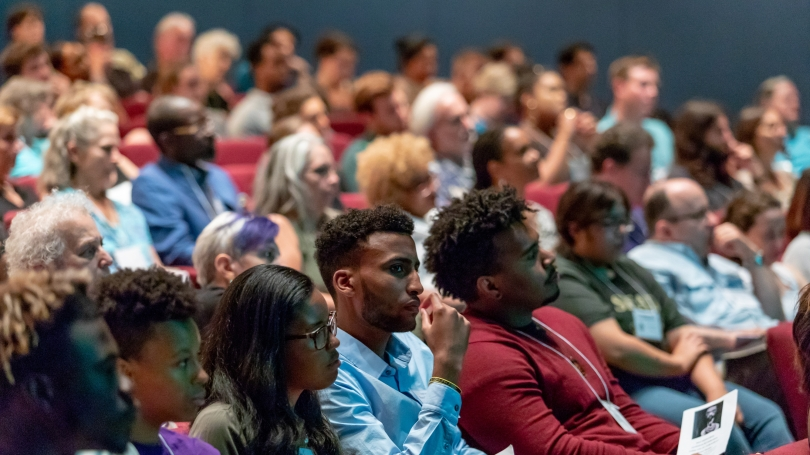 An audience listens to a speaker in an auditorium.